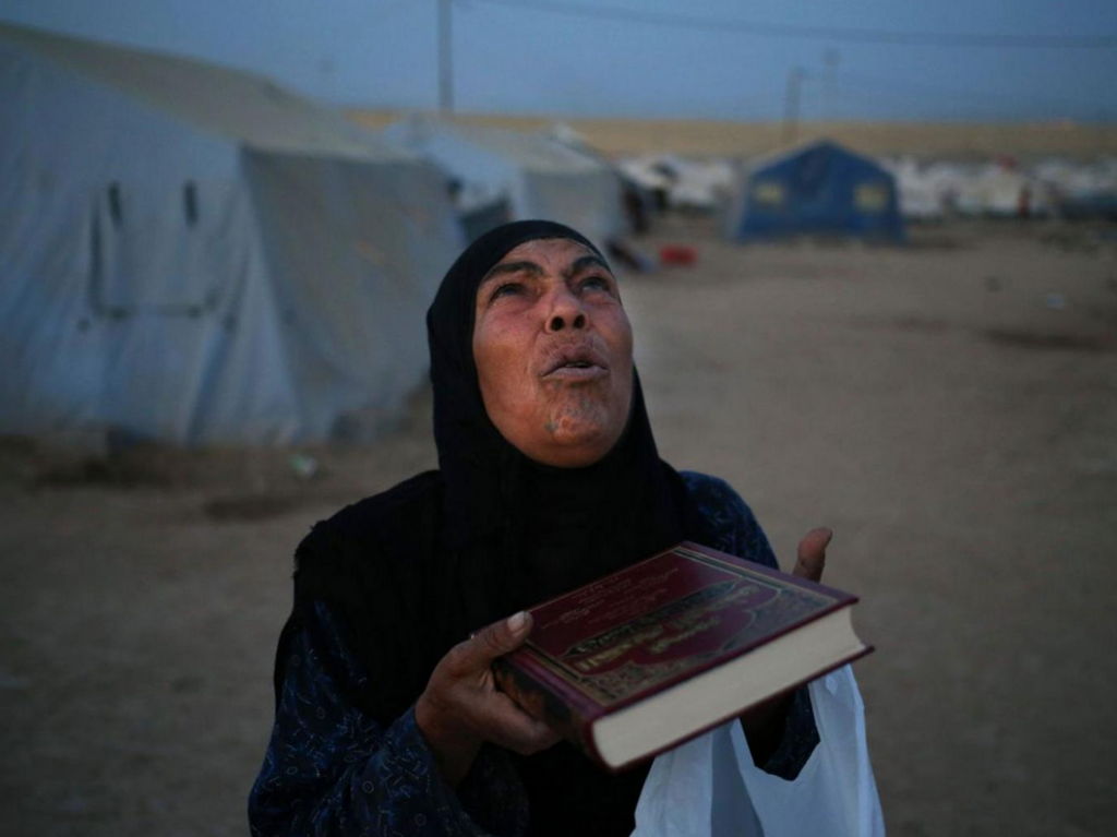 Iraqi woman_fled_family_northern city_Mosul_prays with a copy_Quran